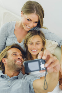 Happy father, mother and daughter taking a selfie on couchの写真素材 [FYI04335856]
