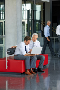 Two businessmen working on laptop in office lobbyの写真素材 [FYI04335865]