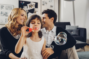 Happy family at home with girl blowing soap bubblesの写真素材 [FYI04335867]
