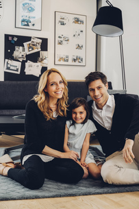 Happy family with daughter sitting on floor in living roomの写真素材 [FYI04335869]