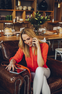 Blond woman with digital tablet sitting in a coffee shop telの写真素材 [FYI04335872]