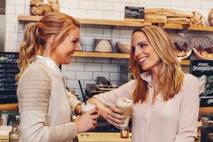 Two female friends drinking Latte Macchiatoの写真素材 [FYI04335873]