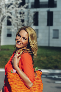 Portrait of smiling blond woman with orange shopping bagの写真素材 [FYI04335874]