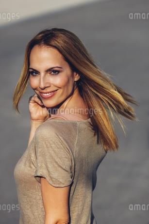 Portrait of smiling blond woman looking over her shoulderの写真素材 [FYI04335875]