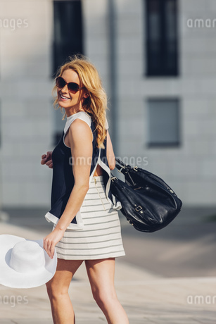 Portrait of smiling blond woman with summer hat and leatherの写真素材 [FYI04335876]