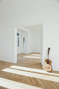 Guitar leaning on wall, empty roomの写真素材 [FYI04335883]
