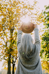Back view of woman holding hat against the sun in an autumnaの写真素材 [FYI04335904]
