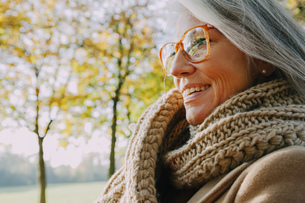 Portrait of smiling woman wearing scarf and glassesの写真素材 [FYI04335906]