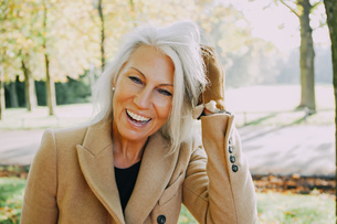 Portrait of laughing woman with hands in her hair in autumnaの写真素材 [FYI04335907]