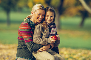 Portrait of mother and daughter together in an autumn parkの写真素材 [FYI04335910]