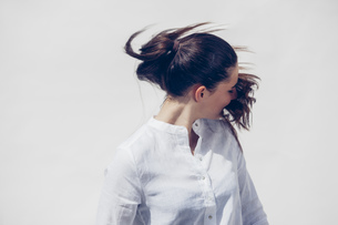 Young woman wearing white blouse tossing her ponytail in froの写真素材 [FYI04335911]