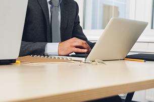 Businessman sitting at desk using laptopの写真素材 [FYI04335922]