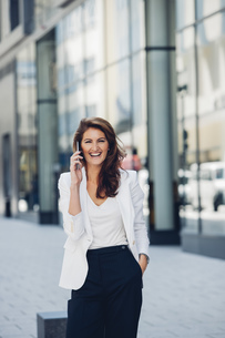 Happy businesswoman outdoors on cell phoneの写真素材 [FYI04335929]