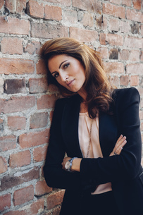 Portrait of smiling businesswoman leaning against brick wallの写真素材 [FYI04335930]