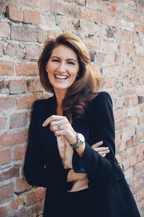 Portrait of happy businesswoman leaning against brick wallの写真素材 [FYI04335931]