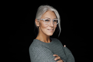 Portrait of smiling woman wearing glasses in front of blackの写真素材 [FYI04335933]