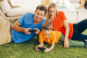 Family of three playing video game in living roomの写真素材 [FYI04335938]