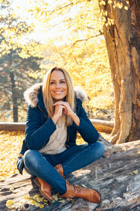 Smiling woman enjoying autumn in a forest sitting on a trunkの写真素材 [FYI04335941]