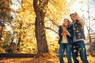 Happy couple having fun in autumn in a forestの写真素材 [FYI04335944]