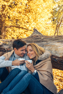 Smiling couple holding cups in autumn forestの写真素材 [FYI04335945]