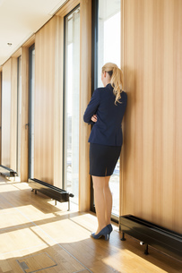 Businesswoman leaning against wallの写真素材 [FYI04335953]