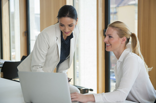 Two businesswomen in office working together on laptopの写真素材 [FYI04335954]