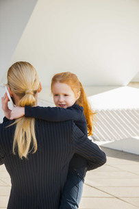 Businesswoman on the phone holding daughterの写真素材 [FYI04335962]