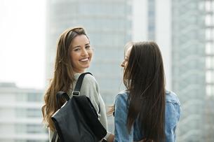 Two girlfriends walking in the city, looking o er shoulderの写真素材 [FYI04335964]