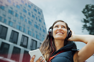 Smiling young woman with headphones and cell phone in the ciの写真素材 [FYI04335968]