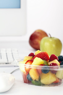 Bowl of fruit salad on office deskの写真素材 [FYI04336036]