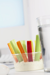 Plastic bowl with Vegetable sticks and dip on office deskの写真素材 [FYI04336039]