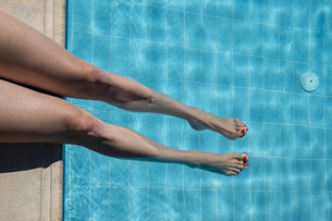 Woman sitting at pool edge with legs in the waterの写真素材 [FYI04336048]