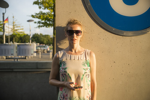 Germany, Berlin, woman standing in front of an underground sの写真素材 [FYI04336051]