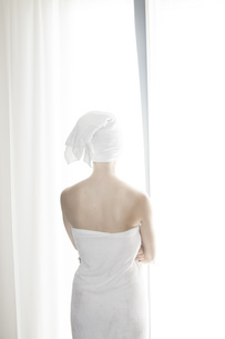 Woman wrapped in white towel standing in front of white curtの写真素材 [FYI04336055]