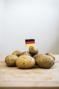 Row potatoes and small german little flag on woodの写真素材 [FYI04336059]