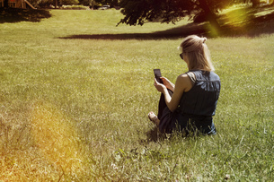 Woman sitting on a meadow of a park using smartphoneの写真素材 [FYI04336067]
