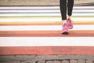 Woman crossing multi coloured zebra crossing, partial viewの写真素材 [FYI04336103]