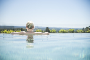 Woman standing in infinity pool, looking at distanceの写真素材 [FYI04336109]