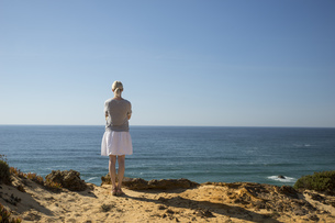 Woman standing at coast, looking at distanceの写真素材 [FYI04336113]