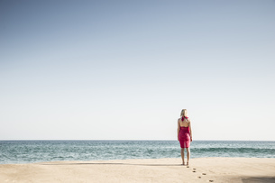 Back view of woman walking on the beachの写真素材 [FYI04336117]