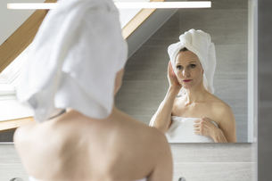Woman looking at her mirror image in the bathroomの写真素材 [FYI04336120]