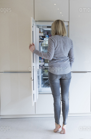 Woman looking into fridgeの写真素材 [FYI04336127]