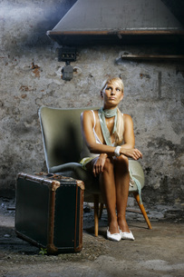 Young woman sitting on armchair, looking upの写真素材 [FYI04336131]