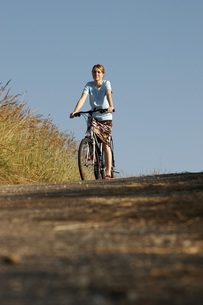 Young woman riding bicycle, low angle viewの写真素材 [FYI04336134]