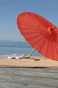 Germany, Bavaria, Lake Starnberg, parasol and bathing shoesの写真素材 [FYI04336142]