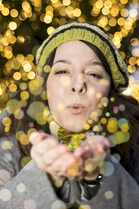 Portrait of young woman blowing golden glitterの写真素材 [FYI04336158]