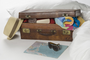 Suitcase with map on bedの写真素材 [FYI04336225]