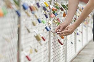 Germany, Bavaria, Munich, Man locking love lockの写真素材 [FYI04336233]