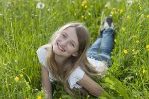 Germany, Bavaria, Portrait of girl lying on meadow, smilingの写真素材 [FYI04336235]