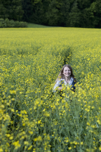 Germany, Bavaria, Starnberg, girl in a rape fieldの写真素材 [FYI04336239]